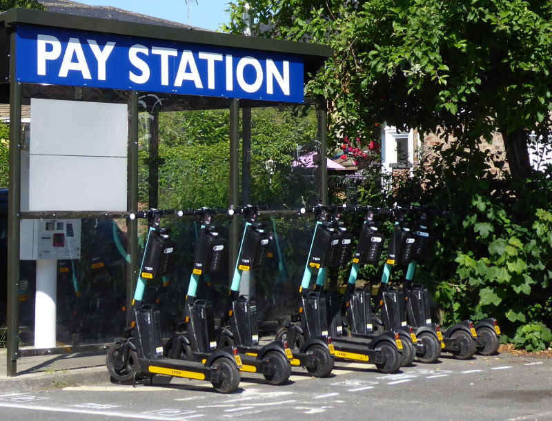 A row of e-scooters parked up at a docking station in a car park